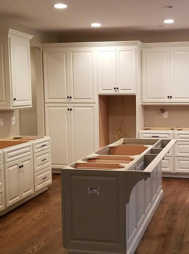 Modern white kitchen design with custom cabinets, kitchen island, and wood floor